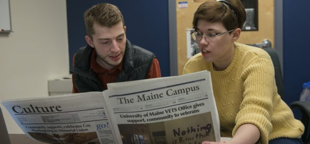 two students reading the Maine Campus Newspaper